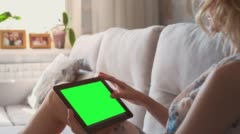Beautiful girl using tablet pc with pre-keyed green screen laying on sofa at Stock Footage