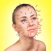 Close-up of performing acupuncture therapy on face - stock photo