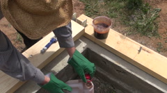 Builder waterproofing wooden plank Stock Footage