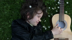 4k Shot of a Cute Child Outside Playing Guitar on the Grass Stock Footage