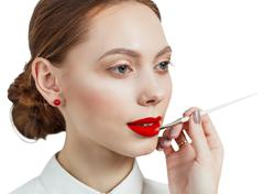 Young woman applying lipstick with an applicator - stock photo