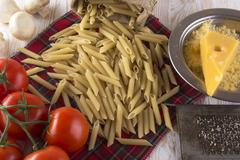 Pasta, tomatoes, champignon and grated cheese. Stock Photos