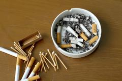 Smoked cigarettes in white ashtray and matchstick Stock Photos