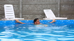 Young man relaxing in the swimming pool on sunny day Stock Footage