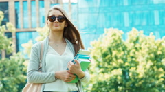 Student girl holding her books and tablet pc on urban space Stock Footage