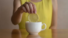 Woman putting lemon into tea - stock footage
