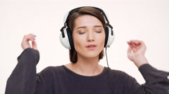 Portrait of young pretty girl listening music in headphones, singing and dancing - stock footage