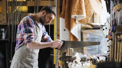 Carpenter working with saw and wood at workshop Stock Footage