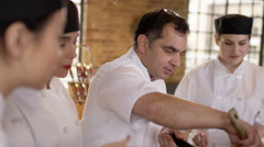 4K Professional chef with trainees in kitchen, demonstrating how to prepare meal Stock Footage