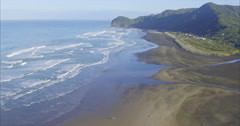 Aerial over ocean surf and beach at piha, Auckland, New Zealand Stock Footage