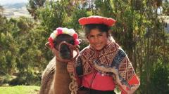 A peruvian girl poses with a llama near ollantaytambo Stock Footage