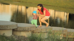 Happy mother and son traveling in nature park, river on sunny day. Woman, little - stock footage