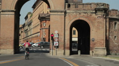 Man riding his bycicle across medieval gate in Bologna Stock Footage