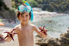 Little boy holding red five point starfishes in his hands on the beach - stock photo