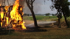 Fireman spraying water on ground near house on fire Stock Footage