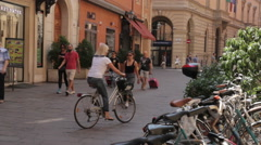 An Adult Blonde Woman rides his bicycle in Bologna, Italy Arkistovideo