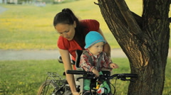 My mother takes care of a beautiful baby boy in a bicycle seat in the park Stock Footage