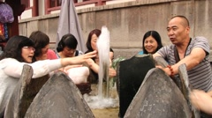 Asian tourists wash hands in the Huaqing hot springs water in Xian, China. Stock Footage