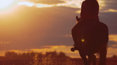Young woman riding horse into bright sunset Stock Footage