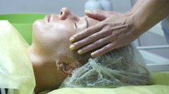 Beautician hands stroking the face of the client. Facial massage beautiful girl. - stock footage