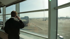 Airport Security Officer in uniform watching aerodrome traffic and talking on Stock Footage
