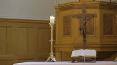 Candlestick holders with crucifix and bible on table in church Stock Footage