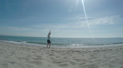 Woman making cartwheel on the beach Stock Footage
