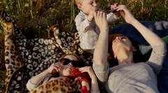 mother and children lie on plaid in field. Slow mo - stock footage