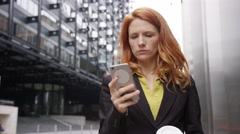Businesswoman in city using smart phone with takeaway coffee Stock Footage