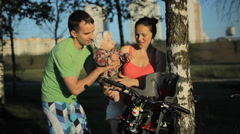Young mother and father of a beautiful baby boy sit down in a chair in a bicycle Stock Footage