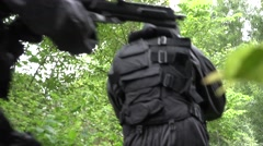 A Special Force Team walk through a wilderness area with weapons in ready. Stock Footage