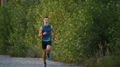 Strong muscle runner man running in park at dusk, slow-motion, wide angle Stock Footage