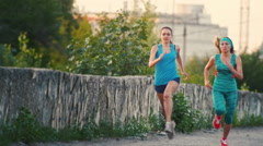 Two young beautiful woman running at city park , slow-motion Stock Footage