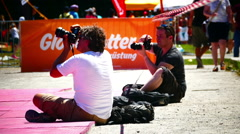 Photographers shooting sport event in hot sunny day Stock Footage