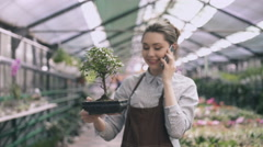 Gardener in apron talking on phone and holding plant in pot Stock Footage