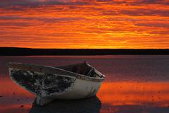 Boat against sunset montage Stock Photos