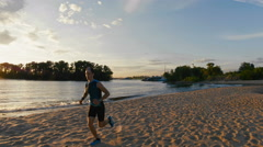 Strong male runner at the beach takes a break to get his breath back Stock Footage
