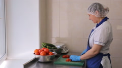 Woman in apron and gloves cut tomatoes and cucumbers Stock Footage