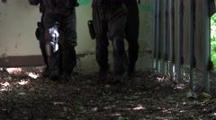 Four Special Soldiers walk along outside at some bedraggled kennels. Close up Stock Footage