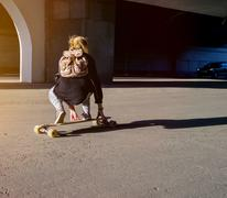 Young girl riding on a longboard on a paved road in summer time in city Stock Photos