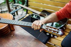 Man takes a classical acoustic guitar in the hand, lying on the wooden table Stock Photos
