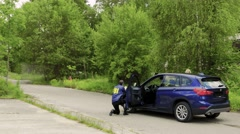 A Special Force Squad storm in a house while two with FBI agents stand at a car. Stock Footage
