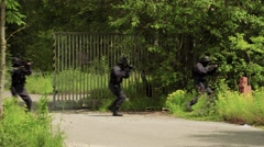A Special Force Troop walk with weapons in ready over a street. Stock Footage