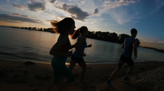 A group of athletes - two girls and a guy runs on beach, near river at sunset Stock Footage
