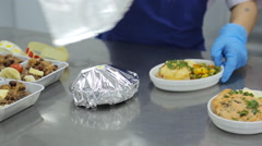 Worker, factory catering, wraps food in foil and mark with a sticker Stock Footage