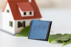 close up of house model and solar battery or cell - stock photo