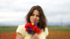 Beautiful girl offers collored bouquet, flower in focus woman blur in background Stock Footage