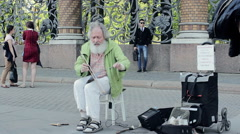 Strange Old Man Playing The Saw Like A Violin. Concert On The Street Stock Footage