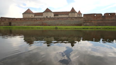 Beautiful fortress surrounding castle, mirroring in lake, water waving Stock Footage