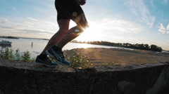 Running man in park at sunset, close-up, slow-motion, silhouette Stock Footage